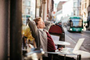 Businessman using laptop at sidewalk cafe